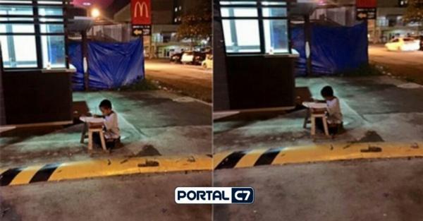 A foto que emocionou o mundo: menino, morador de rua, usa a luz do McDonald's para fazer lição de casa